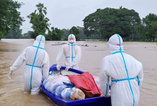 မိုးဆက်တိုက်ရွာလို့ ရေဘေးဒဏ်ခံနေရတဲ့ ကရင်ပြည်နယ် လှိုင်းဘွဲ့မြို့နယ်မှာ ဇူလိုင်လ ၂၈ ရက်နေ့က ကိုဗစ်-၁၉ ကူးစက်သေဆုံးသူတစ်ဦးကို သဂြိုဟ်ရန် သယ်ဆောင်လာစဉ်။